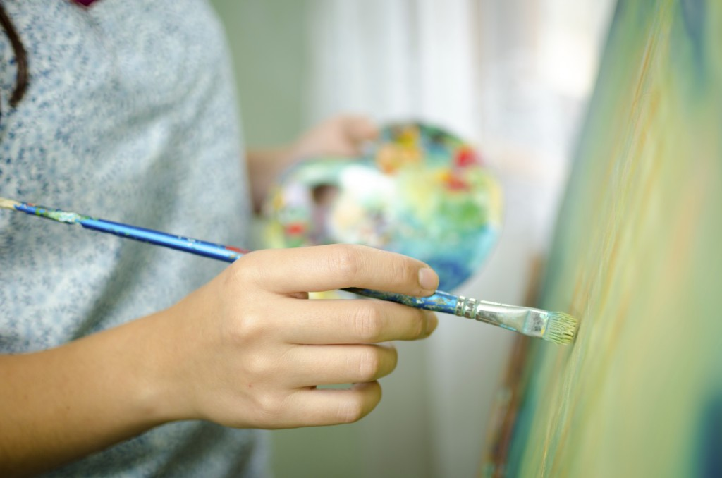 Artist applying paint to a canvas
