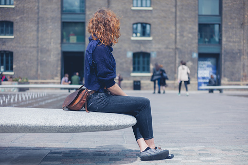 Young woman sitting on granite bench