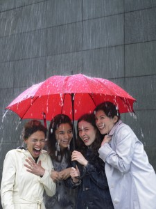 Four women sharing umbrella in the rain