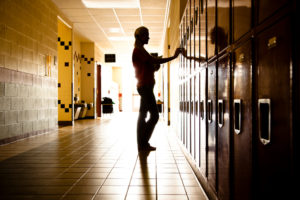 Silhouette of student standing in hallway by lockers