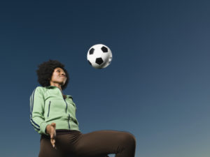 African woman kneeing soccer ball