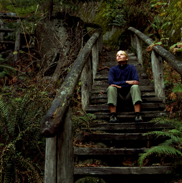 Young woman in forest, sitting on wooden staircase, looking upward