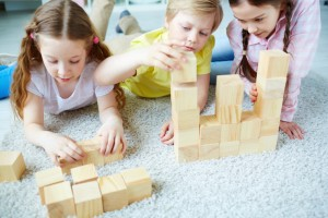 Two girls and one boy playing with wooden blocks