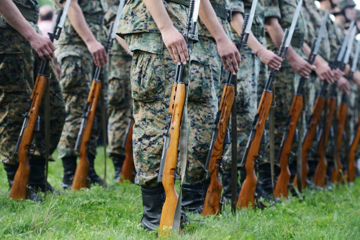 Military members in camouflage uniforms lined up
