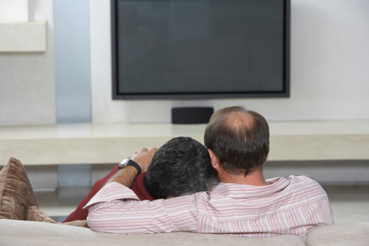 Couple Sitting on Sofa with Television Off