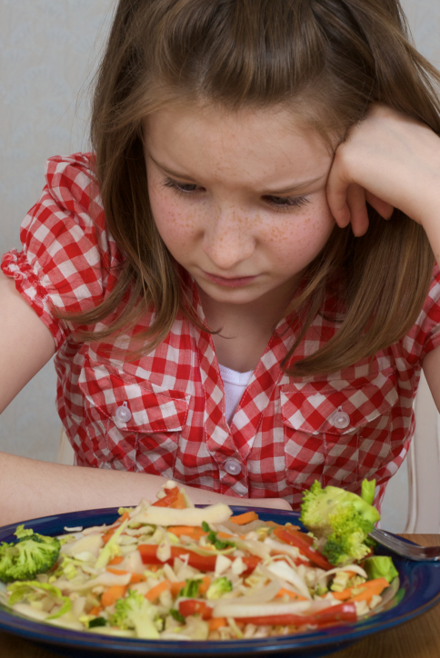 Young girl looks down sadly at plate of food