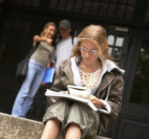 Blonde preteen sits on school steps reading while kids behind point