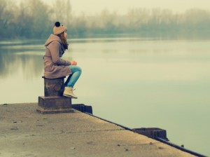 Girl sits on dock looking out at water