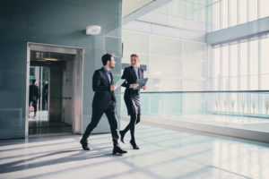 Two business associates walk down corridor having discussion
