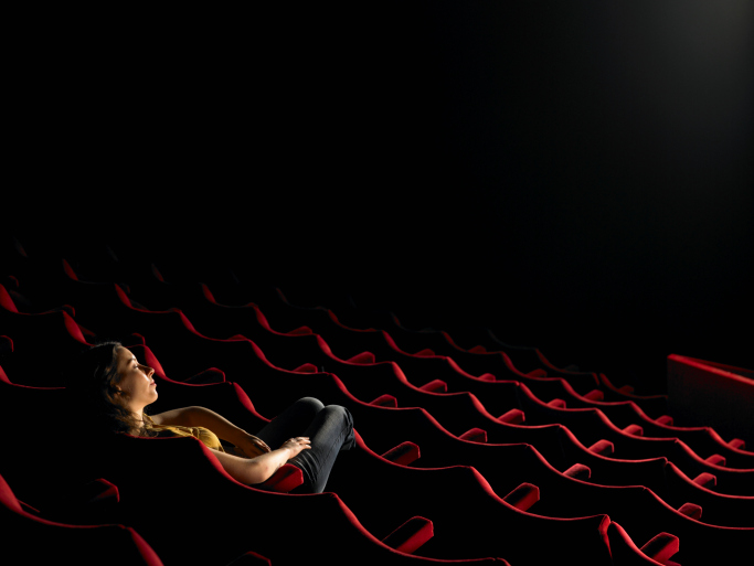 Young woman sitting in empty cinema, elevated view