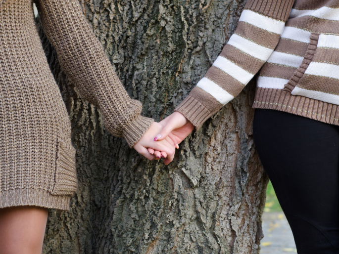 Same-sex couple holding hands against a tree