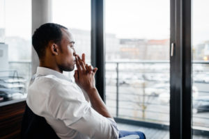 Person sits at desk looking out window thinking in open office space