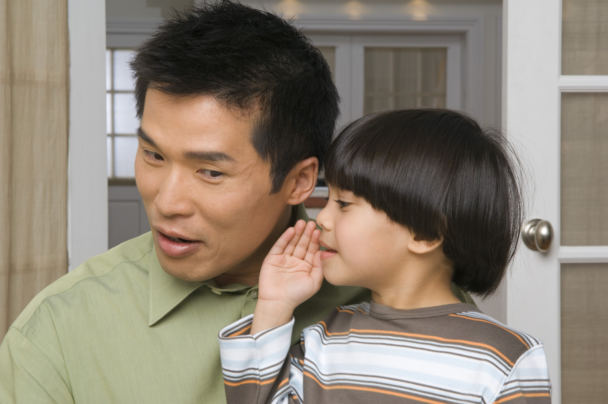 Son whispering into father's ear