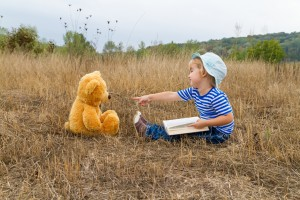 Child reads book with stuffed bear in field