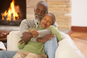 Senior African couple hugging on the sofa