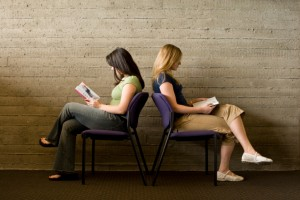 Two women read books, facing away from each other.