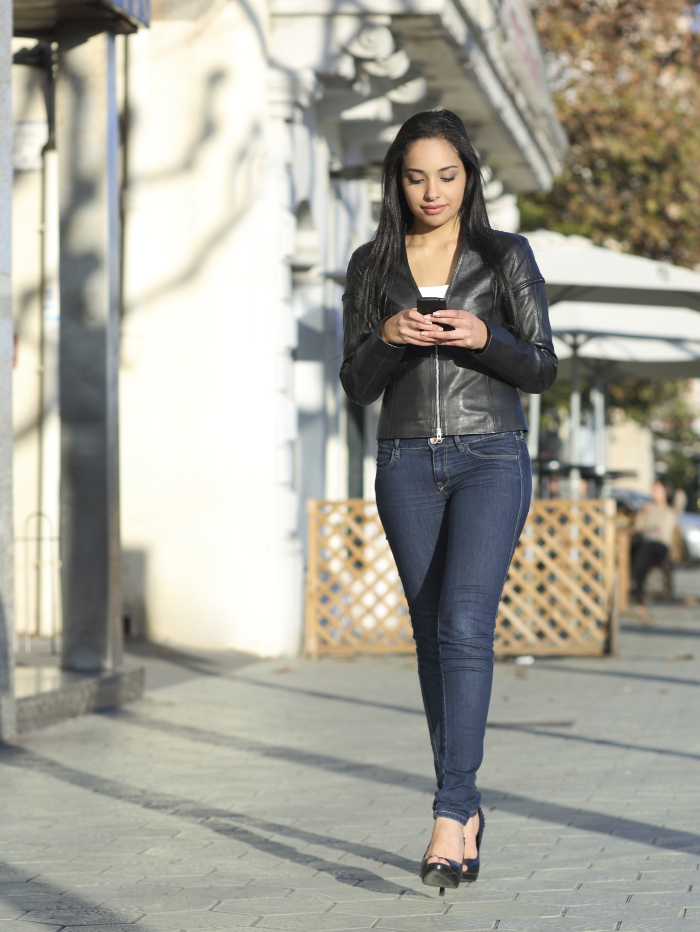 Woman texting on a smartphone while walking