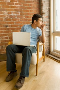 Young man with laptop looks lost in thought