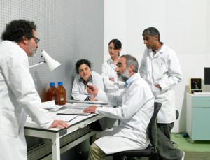 Researchers discussing something around a desk