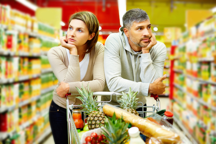 An unhappy couple leans on cart in supermarket