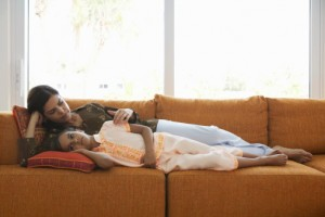 Mother lying on sofa with daughter