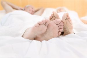 closeup on feet of couple lying in bed
