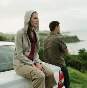 Couple looks at coastline, man stands, woman sits on back of car