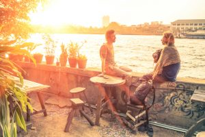 couple sits on patio talking at sunset