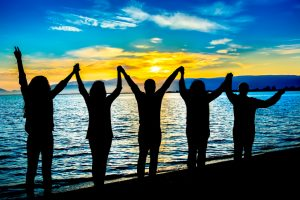 Group of people on beach at sunset raising linked hands to sky