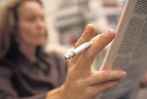 Close-up of cigarette while reading the newspaper