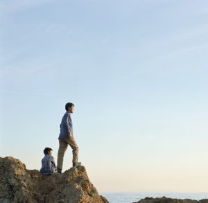 Man stands on rock cliff looking out to see while child sits behind him