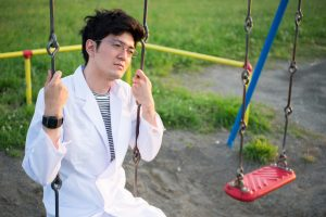 Person in white lab coat sits on swing looking thoughtful