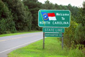 An empty road with a 'Welcome to North Carolina' sign