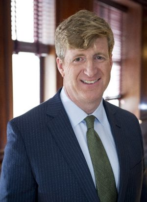 Patrick Kennedy standing in front of a window wearing a suit