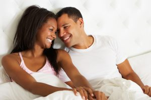 Smiling couple cuddles in bed