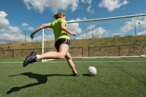 Woman about to kick soccer ball into net