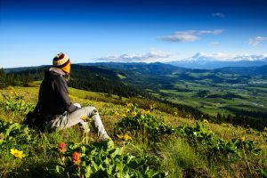 Person sits in meadow on hillside