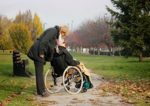 Person looks down to check on older person in wheelchair outdoors on windswept path
