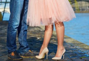 Cropped view of legs of two people, one wearing a tulle skirt and heels, one wearing jeans