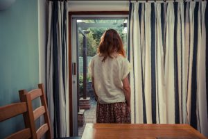Rear view of person standing by curtains of French doors and looking out