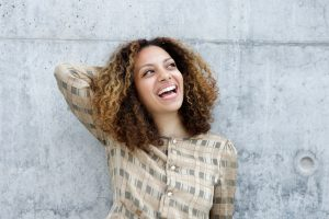 Laughing young person with shoulder-length natural hair stands against concrete wall