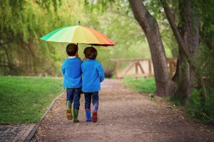 Two boys in blue jackets and rain boots walk together under rainbow umbrella