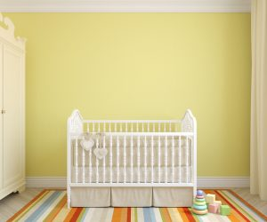 A white crib sits in a bright nursery with yellow walls and striped rainbow rug