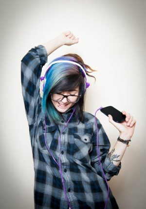 Young adult with headphones and brightly dyed hair listens to music
