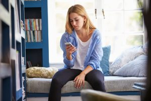 Woman sitting on bed while looking at phone