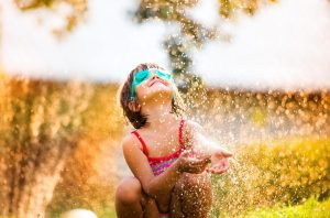 Young child in goggles plays in sprinkler with carefree smile