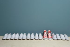 One pair of red shoes stands out in row of white shoes along wall