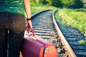 Cropped view of person holding red suitcase stands near train tracks waiting for train