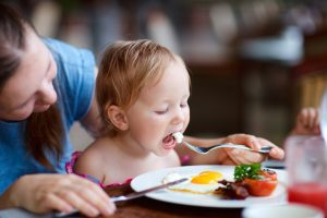 Woman helping child eat eggs at table