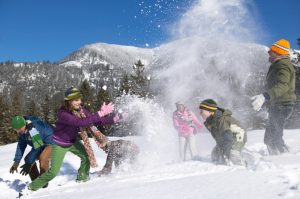 Large group of people of different ages throw snowballs by hills under blue sky